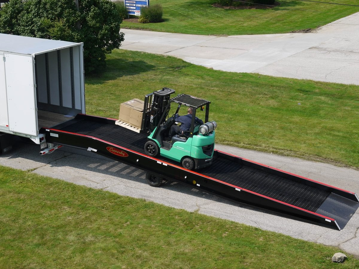 A forklift utilizing a Copperloy forklift ramp.