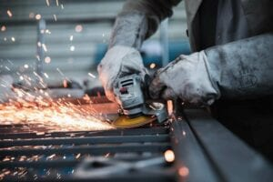 Industrial Website Design Near Me | Craftsmen grinding something with power grinder causing sparks to fly