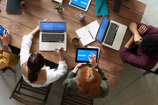 ADVAN SEO Web Design Services   A team working on laptops with blue screens at a large table